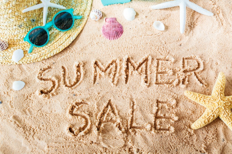 Summer Sale text in the sand with beach accessories
